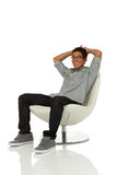 Young adult relaxing on a modern chair Royalty Free Stock Photo