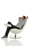 Young adult relaxing on a modern chair looking up Royalty Free Stock Images