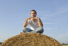 Young adult sitting on a straw bale Stock Image