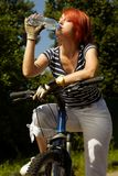 Young adult smiling biker woman on mounting bike Royalty Free Stock Photos