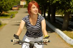 Young adult smiling biker woman on mounting bike Stock Photography