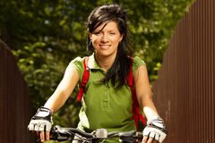 Young adult smiling biker woman on mounting bike Royalty Free Stock Photo