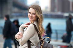 Young adult smiling student girl walking on city with many people around wearing sweater and carrying backpack
