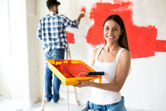 Young adult woman holding roller and paint for painting home. Young adult smiling women holding roller and paint for painting home royalty free stock images
