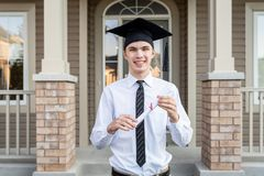 Young male student holding a diploma while wearing a graduation cap in front of a house. Young Adult/Student in front of his house after his graduation ceremony stock photography