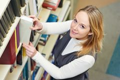 Young adult student selecting book Royalty Free Stock Photos