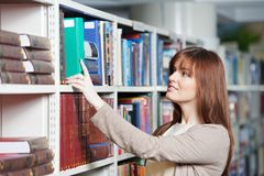 Young adult student selecting book in library Royalty Free Stock Photos