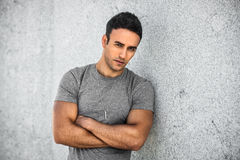 Young adult stylish handsome man with bristle standing outdoors and leaning on wall with arm crossed wearing grey casual t-shirt. Portrait of young adult stylish royalty free stock image