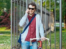 Young adult talking on mobile phone. Young adult man talking on mobile phone on urban city park background Royalty Free Stock Photo