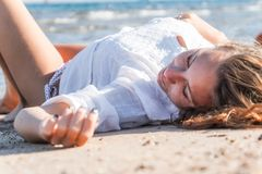 Young adult tanned blond girl lies on the sand on the beach near royalty free stock photo