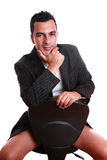 Young adult on thirties. Sensual man (young adult on thirties) sitting in a chair, isolated on white Royalty Free Stock Image