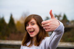 Young Adult Thumbs Up. Beautiful girl doing a thumbs up sign with her hand and fingers for this unique approval image Stock Photos