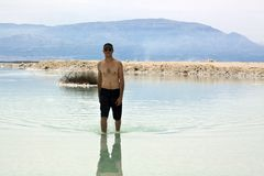 Tourist at Dead Sea. A young adult tourist walking in the shallow waters of the Dead Sea, Israel Stock Image