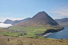 View to the majestic Malinsfjall mountain and Viðareiði settlement on the Viðoy island of the Faroe Islands. Young adult unidentifiable woman in bright royalty free stock photography