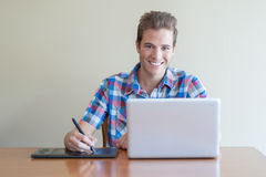 Young adult using computer and touch input tablet. Young male adult using computer and touch input tablet Stock Images