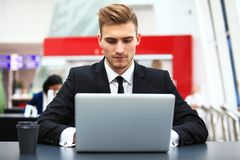Young adult using laptop in airport lounge. Young adult businessman using laptop in airport lounge Stock Photos