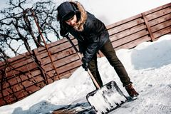 Portrait of young adult using snow shovel and cleaning snow in backyard or driveway. Young adult using snow shovel and cleaning snow in backyard or driveway stock photo