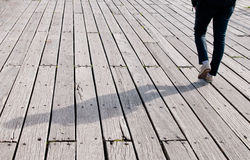 Young adult walking on a wooden footpath Royalty Free Stock Images