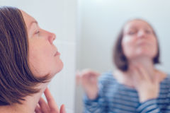Young adult woman applying anti-aging cream Stock Image