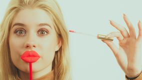 Woman applying lipstick or lip gloss. Young adult woman applying lipstick or lip gloss, getting her make up done holding fake lips on stick Stock Photo