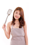Young adult woman with apron, hand holding spatula Stock Photo