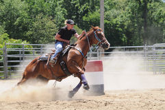 Young adult woman barrel racing. Young adult woman galloping past a barrel stock photo