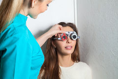 Young adult woman checks vision in an ophthalmologist with corre Royalty Free Stock Images