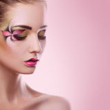 Young adult woman with closed eyes and creative makeup on pink b. Ackground in studio Royalty Free Stock Photos