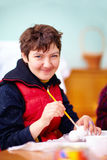 Young adult woman with disability engaged in craftsmanship in rehabilitation center Stock Photos