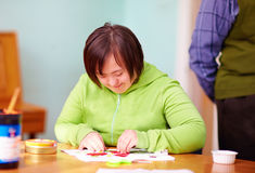 Young adult woman with disability engaged in craftsmanship in rehabilitation center. Young woman with disability engaged in craftsmanship in rehabilitation Royalty Free Stock Photo