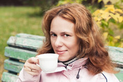 Young adult woman drinks coffee, outdoor photo Stock Photo