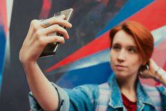 Young adult woman with dyed red hair doing selfie with her smartphone. Selective focus, toned image stock images