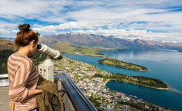 Young adult woman enjoy a stunning view of Queenstown. Through the binocular from view point of the Skyline Gondola Stock Photography