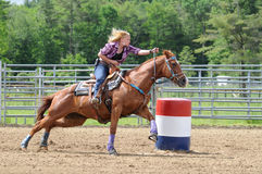 Young adult woman galloping around a turn in a barrel race. Young adult woman galloping turning around a barrel in a barrel race stock photography