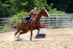 Young adult woman galloping through a turn in a barrel race Stock Images