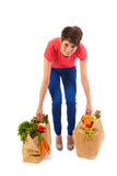 Young adult woman with heavy shopping bags. Pretty young woman with heavy bags healthy vegetables and fruit isolated over white background Royalty Free Stock Photo