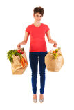 Young adult woman with heavy shopping bags. Pretty young woman with heavy bags healthy vegetables and fruit isolated over white background Stock Photography