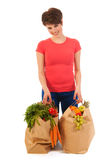 Young adult woman with heavy shopping bags. Pretty young woman with heavy bags healthy vegetables and fruit isolated over white background Stock Photo