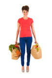 Young adult woman with heavy shopping bags. Pretty young woman with heavy bags healthy vegetables and fruit isolated over white background Royalty Free Stock Image
