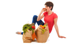 Young adult woman with heavy shopping bags. Pretty young woman with heavy bags healthy vegetables and fruit is resting and eating an apple isolated over white Royalty Free Stock Images