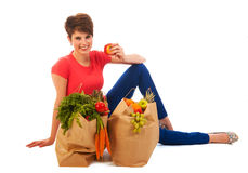 Young adult woman with heavy shopping bags. Pretty young woman with heavy bags healthy vegetables and fruit is resting and eating an apple isolated over white Stock Photos