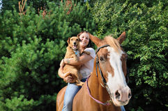 Young adult woman with her horse and dog