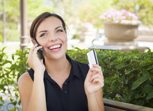 Young Adult Woman Holding Cell Phone and Credit Card Outside Royalty Free Stock Images