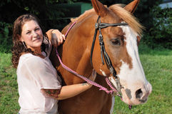 Young adult woman holding her horse Stock Images