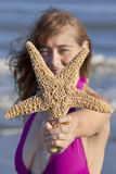 Young adult woman holding a starfish. Young adult woman in a swimsuit holding a starfish and looking at ocean Off center for copy space royalty free stock photos