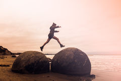 Young adult woman jumping on Moeraki Boulders, South Island New Stock Photography