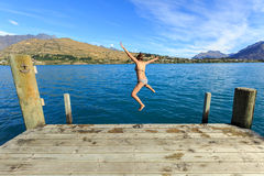 Young adult woman jumping in to the lake with joyful Stock Image