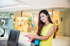 Young adult woman paying currency for purchases Royalty Free Stock Photography
