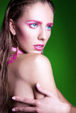 Young adult woman with pink make up on green background Royalty Free Stock Photography