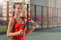 Young adult woman with racket and bottle on the tennis court Stock Photo
